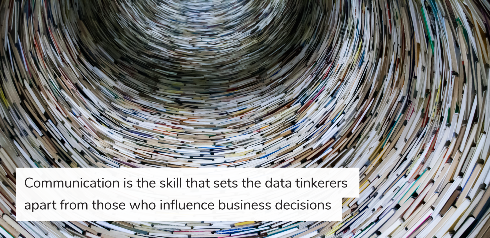 "Tower of books with overlaid text ""Communication is the skill that sets the data tinkerers apart from those who influence business decisions"""
